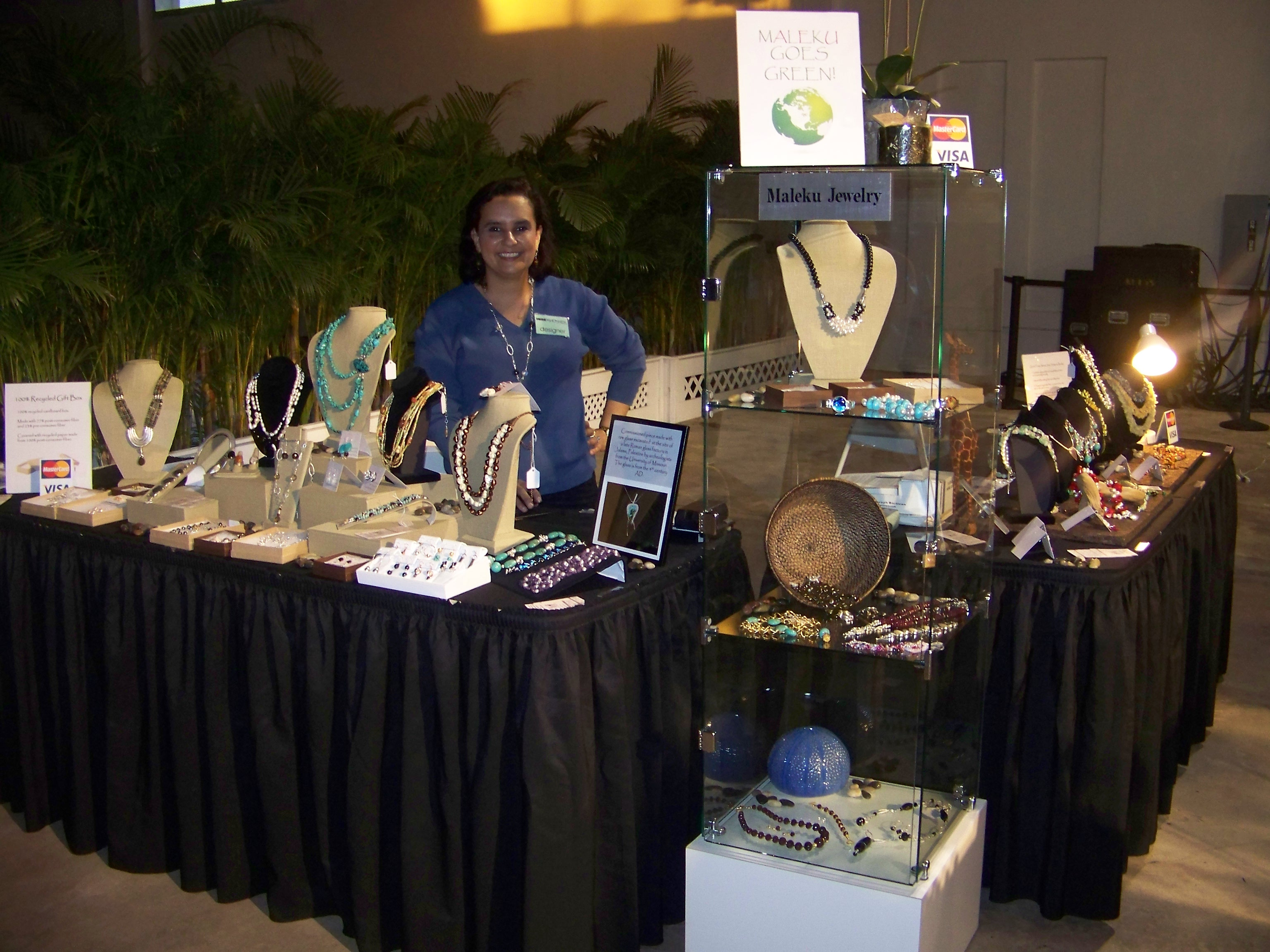 Ileana Maleku posing with her Maleku Jewelry display at Miami Fashion Week