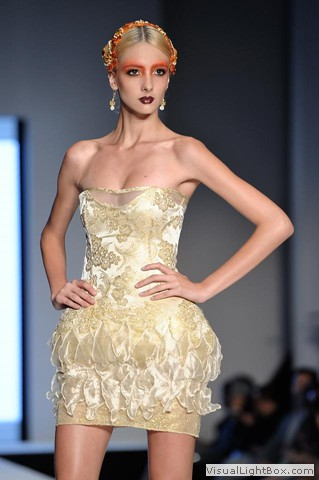 Runway model in gold dress wearing Maleku Jewelry and accessories at Miami International Fashion Week