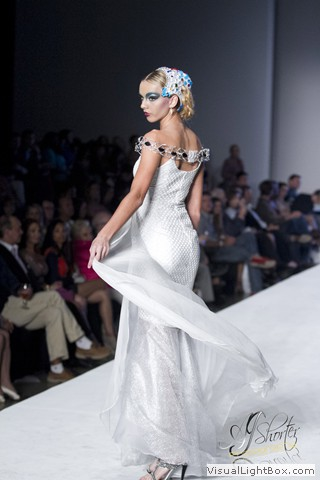 Runway model in white wearing a blue headpiece by Maleku Jewelry at Miami International Fashion Week